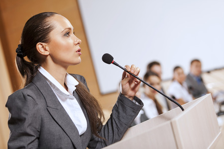 public speaking: Businesswoman standing on stage and reporting for audience Stock Photo