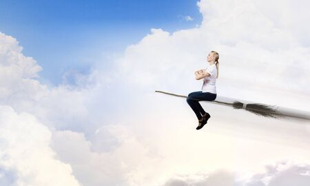 sorcery: Young girl in casual flying on broom high in sky Stock Photo