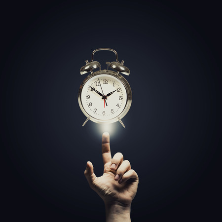 classical mechanics: Close up of man hand pointing at clock watch symbol