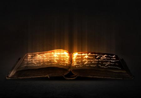 페이지에 조명과 함께 오래 된 검은 마법의 책