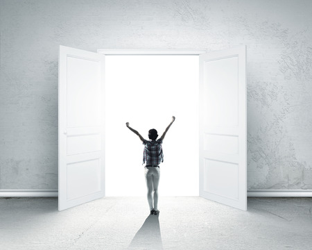 puerta abierta: Vista trasera de la mujer con las manos en alto entrando puerta abierta Foto de archivo