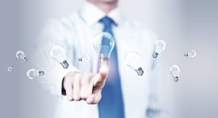 activating: Close up of businessman touching with finger virtual light bulb Stock Photo