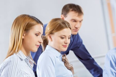 business ideas: Three co-workers discussing business ideas in office