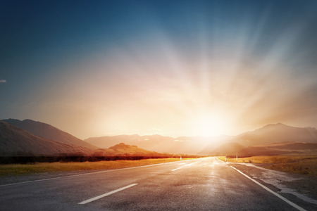 sol naciente: Vaciar la carretera de asfalto y el sol naciente en el horizonte