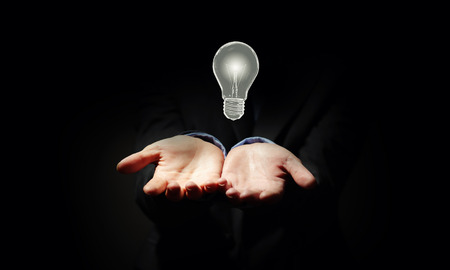 solve problem: Close up of businessman holding symbol of  light bulb