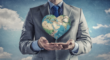 business life: Young businessman holding Earth planet in hand.  Stock Photo