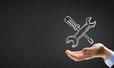 Businessmans hand holding tools over gray background Stock Photo
