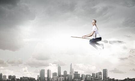 besom: Happy young woman flying in sky on broom