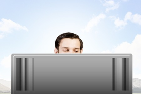 man looking out: Young man looking out above laptop monitor