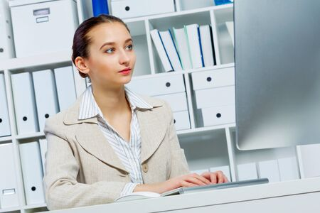 office workers: Attractive woman working in office on computer Stock Photo