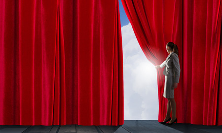 Young businesswoman opening stage curtain to another reality Foto de archivo