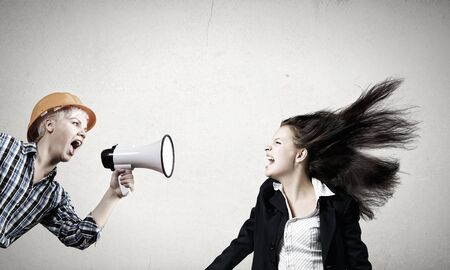 agression: Young furious woman screaming agressively in megaphone