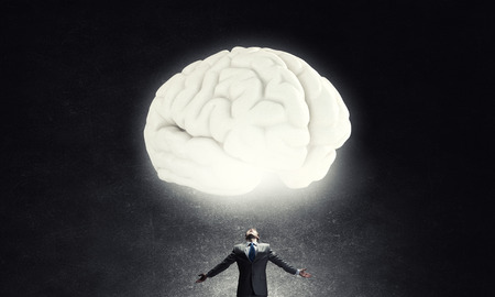 solver: Businessman with hands spread apart and big human brain Stock Photo