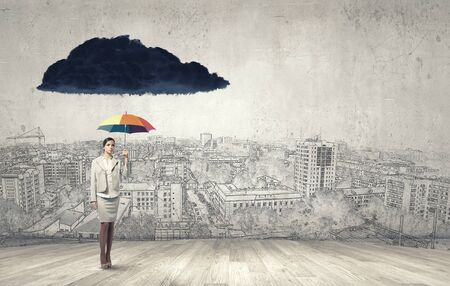 anti season: Young businesswoman with colorful umbrella under black cloud Stock Photo