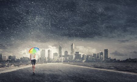 anti season: Young pretty businesswoman with rainbow colorful umbrella walking in storm