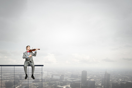 parapet: Young man in suit sitting on parapet and playing violin Stock Photo