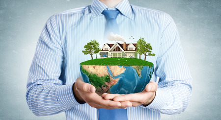 immovable: Close up of hands presenting model of green countryside life. Elements of this image are furnished by NASA