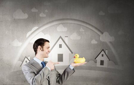 ambivalent: Funny businessman with yellow rubber duck toy
