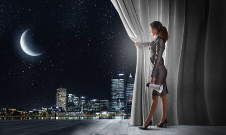 stage curtain: Young businesswoman opening stage curtain to another reality Stock Photo