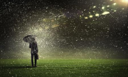sotto la pioggia: Back view of businessman with umbrella standing under rain