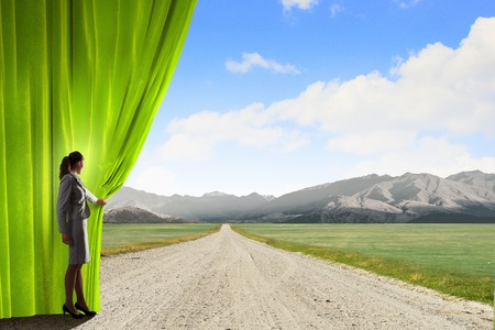 Businesswoman opening curtain to new roads and opportunities Stock Photo