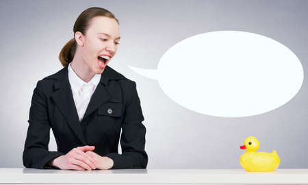 decoy: Young businesswoman and yellow rubber duck toy on table Stock Photo