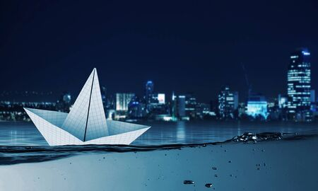 clear away: Boat made of paper sailing on blue water surface Stock Photo