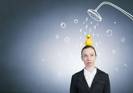 Young businesswoman and yellow rubber duck toy on head