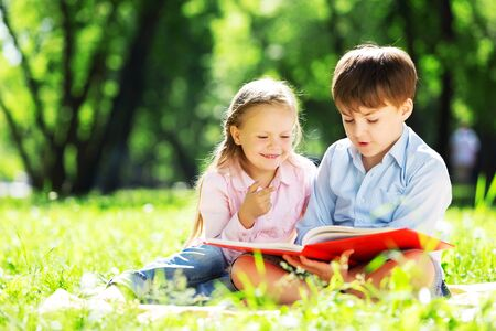 brother: Sister and brother in the park reading a book