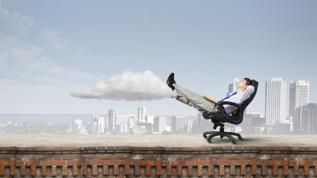 legs up: Young confident businessman sitting in chair with legs up Stock Photo