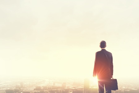 úspěšný: Zadní pohled na podnikatele při pohledu na západ slunce nad městem Reklamní fotografie