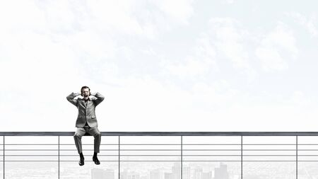parapet: Frustrated businessman sitting on parapet closing ears with hands