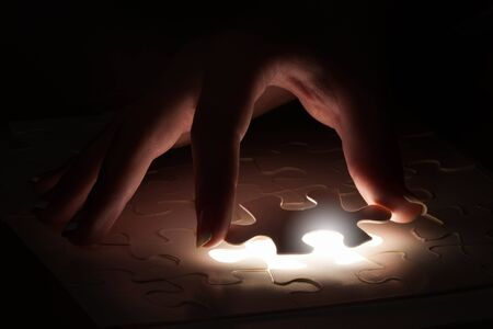 hand to hand: Hand connecting missing jigsaw glowing puzzle piece