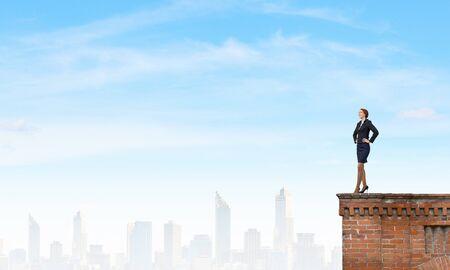 authoritative: Confident pretty businesswoman standing on building top