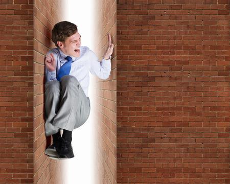 젊은 고생 한 사업가 두 벽 사이에 갇혀