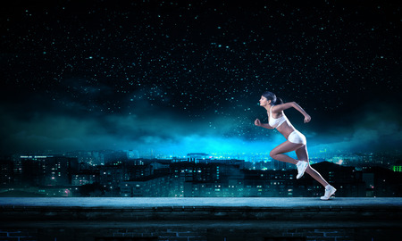 Young woman athlete running fast on dark background 스톡 콘텐츠