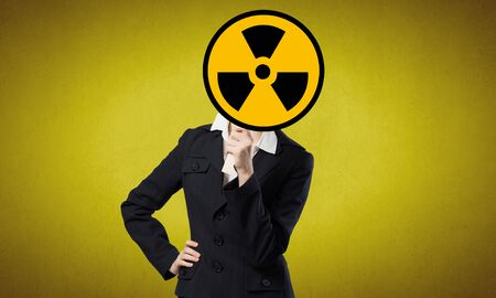 radioactivity: Unrecognizable businesswoman hiding her face behind radioactivity sign