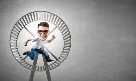 big wheel: Funny picture of running in wheel man with big head over cement background Stock Photo