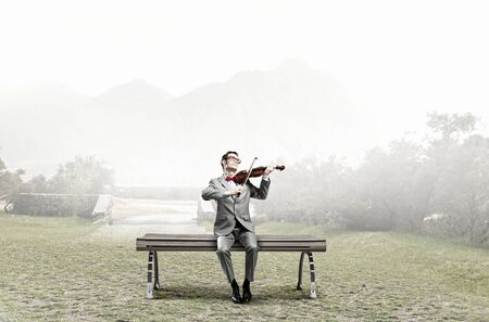 virtuoso: Young man in suit sitting on bench and playing violin