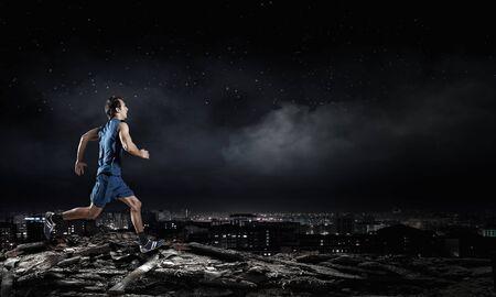 hombre deportista: Hombre joven atleta en desgaste azul al aire libre corriendo