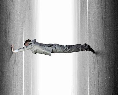 resist: Businessman under pressure between two stone walls