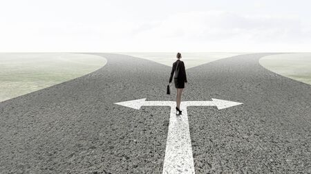 Back view of businesswoman standing on crossroads and making choice Stock Photo