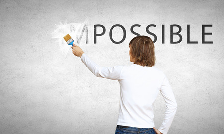 change: Man changing word impossible in to possible by erasing part of word with paint brush Stock Photo