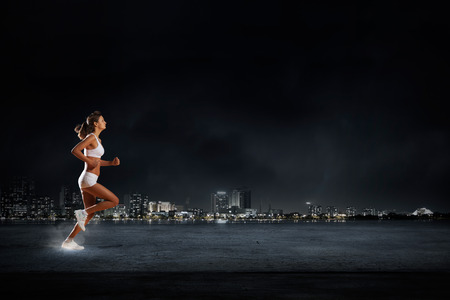Young woman athlete running fast on dark background Stock Photo - 43603295