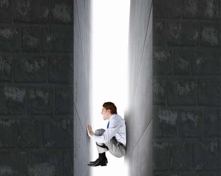 under pressure: Businessman under pressure between two stone walls