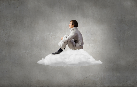 isolation: Businessman in suit sitting on cloud in isolation