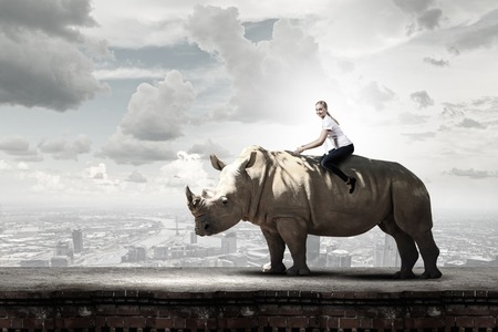 Young pretty fearless woman riding huge rhino