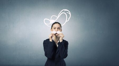 mosquetero: Linda chica feliz que intenta bigote de papel masculino