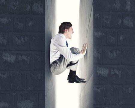 claustrophobia: Young troubled businessman trapped between two walls