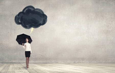 Sfortuna e il concetto di crisi con giovane imprenditrice con ombrello nero